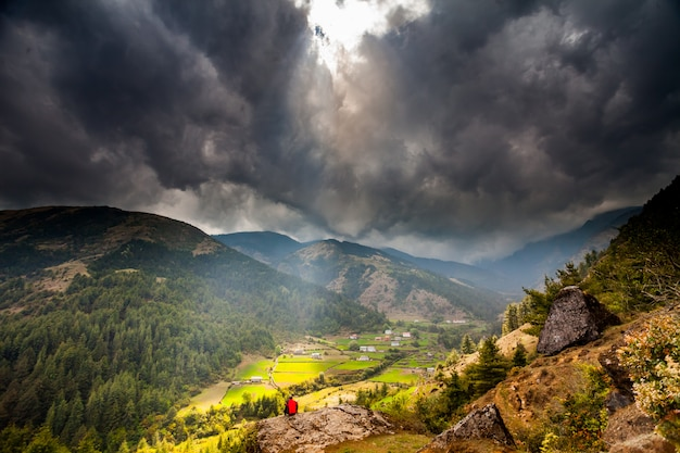 Bergvallei met zonnestralen in bewolkte hemel
