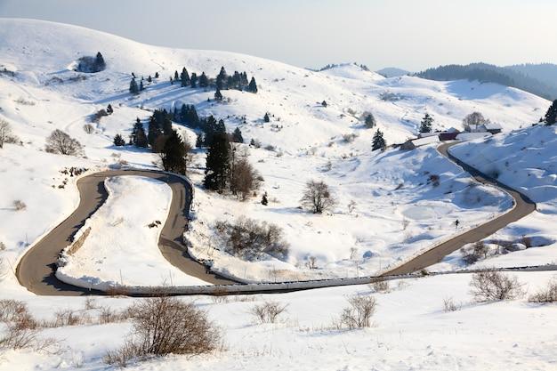 Bergweg met bochten in het winterseizoen. sneeuw en weg