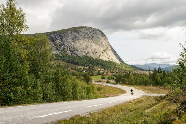 Bergweg met een eenzame motorfiets die naar een berg in setesdal, noorwegen drijven