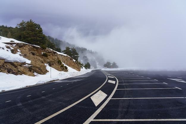 Bergweg met sneeuw en dikke mist. parkeren bij de bergpas. la morcuera.