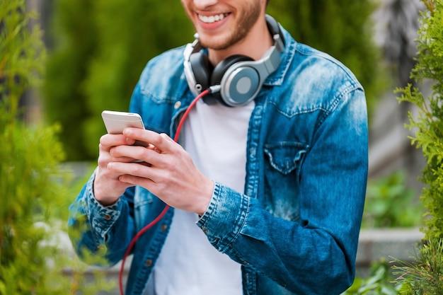 Bericht aan het typen naar een vriend. bijgesneden afbeelding van jonge man die mobiele telefoon vasthoudt en glimlacht