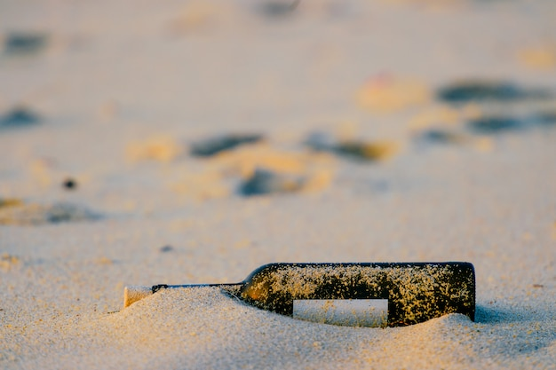 Bericht in glazen fles in zand op strand buitenshuis.