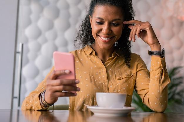 Bericht lezen. glimlachende mooie vrouw die gele blouse met het bericht van de patroonlezing op telefoon draagt