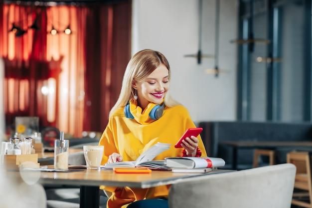 Bericht lezen. vrouw met blauwe oortelefoons en gele trui die een bericht op de telefoon leest