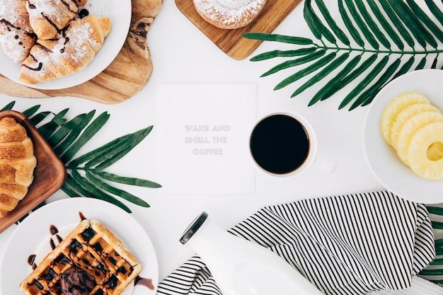 Bericht op blocnote omringd met gebakken ontbijt; koffie en ananas plakjes op witte bureau