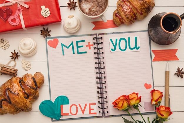 Bericht op de pagina's van de notebook op st. valentijnsdag op de versierde tafel en verrassingsgeschenken