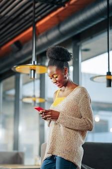 Bericht op telefoon donkerharige vrouw draagt trui met open schouder leest bericht op telefoon
