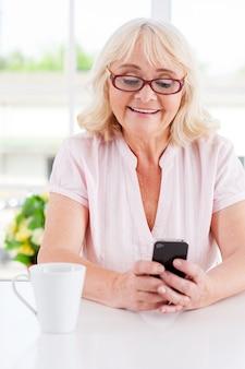 Bericht van haar dichtstbijzijnde. vrolijke oudere vrouw die naar haar mobiele telefoon kijkt en glimlacht terwijl ze aan tafel zit