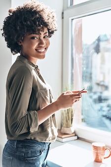 Bericht van vriend. aantrekkelijke jonge afrikaanse vrouw die haar smartphone gebruikt en glimlacht terwijl ze binnenshuis bij het raam staat