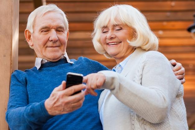 Bericht van zoon. gelukkig senior koppel hecht zich aan elkaar en glimlacht terwijl ze buiten staan en naar de mobiele telefoon kijken