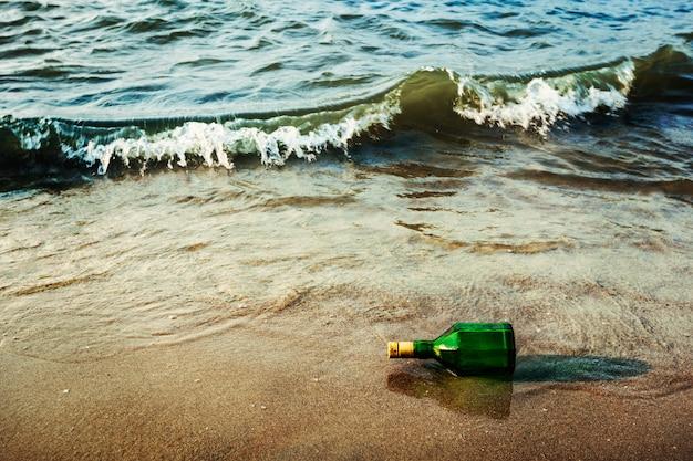 Berichtfles op strand in golven