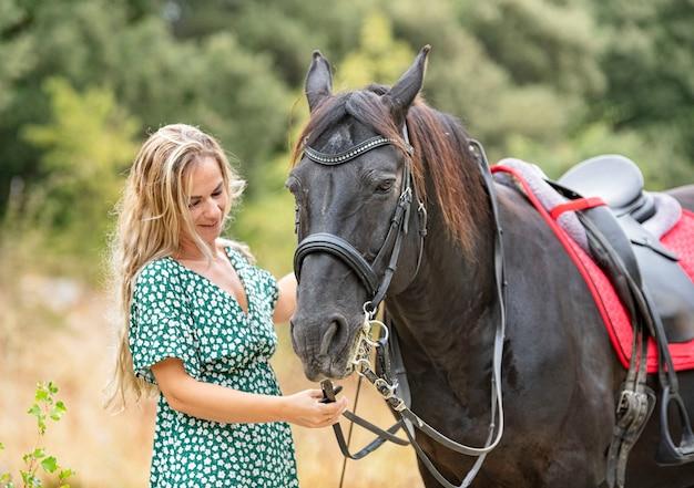 Berijdend meisje loopt met haar zwarte paard