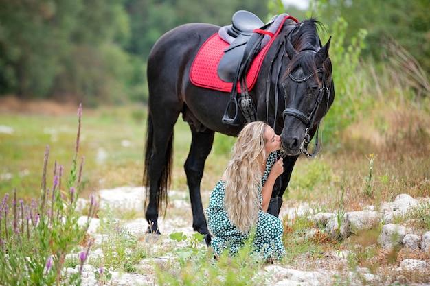 Berijdend meisje loopt met haar zwarte paard Premium Foto