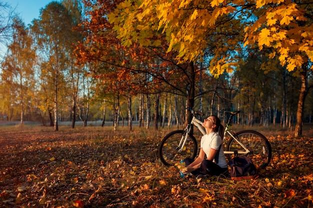 Berijdende fiets in de herfst het bos, jonge vrouwenfietser ontspannen na het uitoefenen op fiets, gezonde levensstijl