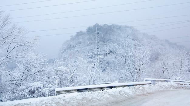 Berijpte hoogspanningsleidingen. distributie station van elektriciteit. winter landschap