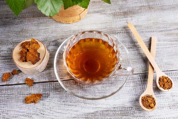Berkchaga chaga helende thee in glazen beker en chaga stukken op houten tafel. alternatief medicijn.