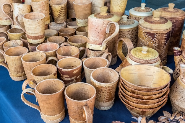 Berkenschorsmokken en -bekers worden verkocht op de volksambachtenbeurs russische volksproducten gemaakt van berkenschors