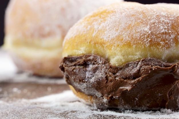 Berlijnse ballen, in brazilië bekend als sonho, gevuld met chocolade, zoals donuts, op een houten tafel met verspreide poedersuiker. selectieve aandacht.
