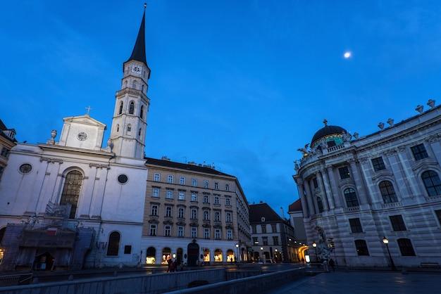 Beroemd hofburg paleis en kerk in de wenen in de avond, gezien vanaf michaelerplatz, oostenrijk
