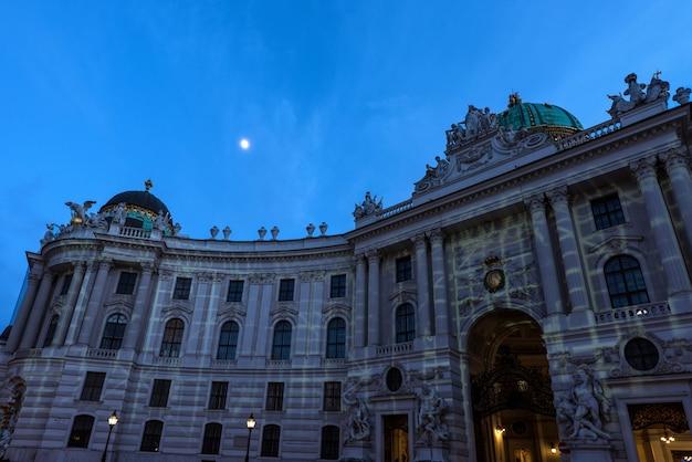 Beroemd hofburg paleis in wenen in de avond, gezien vanaf michaelerplatz, oostenrijk