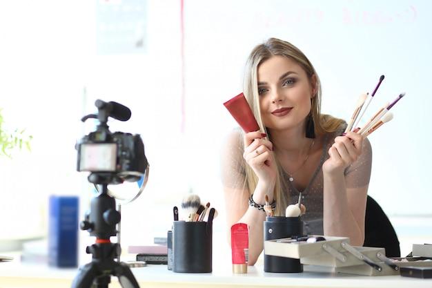 Beroemd make-upproductoverzicht videoblogconcept. prachtige vlogger recording beauty tutorial. cosmetica, gereedschap selectie advies van vrouwelijke blogger. online vertaling thuis of in de studio