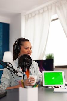 Beroemde blogger-beïnvloeder die video van tablet filmt met groen scherm in podcast thuisstudio. maker van sociale media-inhoud maakt nieuwe series voor haar kanaal en streamt online uitzendingen