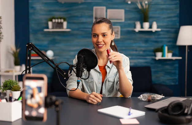 Beroemde blogger die rode lippenstiftrecensie opneemt voor schoonheidsvlog. vrouw vlogger die live make-up tutorial deelt op sociale media met behulp van professionele microfoon die naar camera kijkt voor digitale podcast