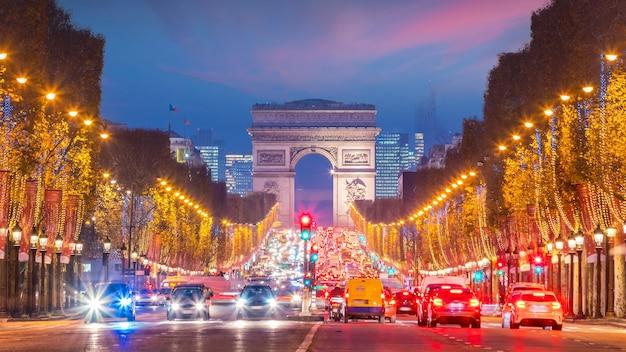 Beroemde champs-elysees en arc de triomphe bij schemering in parijs, frankrijk