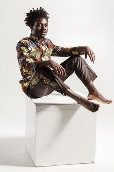 Beroemde en mode afrikaanse man die zich voordeed op kubus