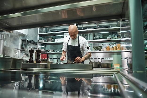 Beroemde jonge chef-kok in zwarte schort aan het werk in zijn moderne restaurantkeuken