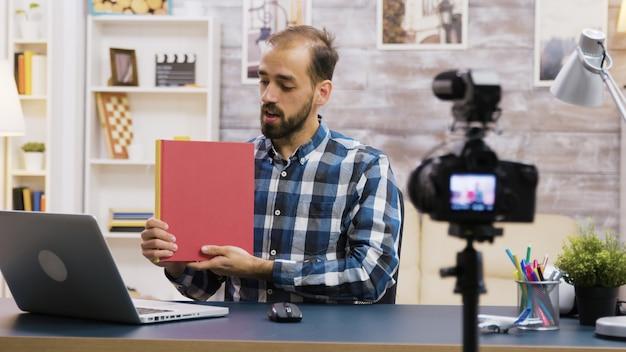 Beroemde jonge vlogger die een recensie van een boek opneemt voor abonnees. vlogger-levensstijl.
