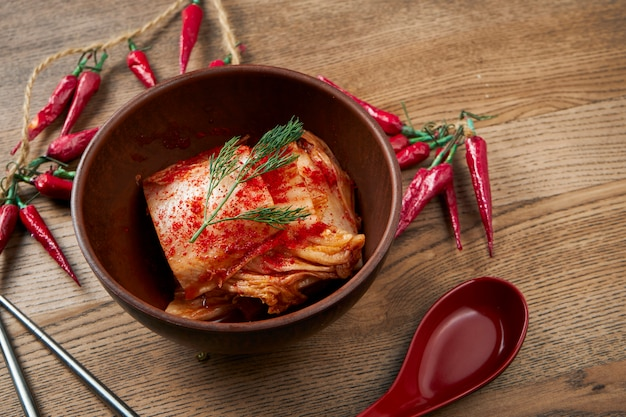 Beroemde koreaanse keuken gerecht - kimchi gezouten en gefermenteerde napa kool in keramische kom op houten oppervlak met kopie ruimte
