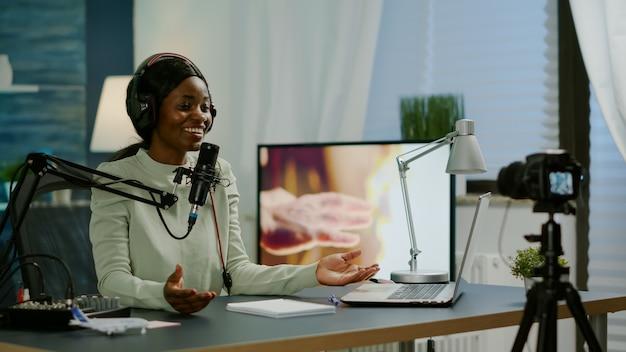 Beroemde vlogger die online podcast-opname maakt voor virtuele show voor de camera. beïnvloeder die hoofdtelefoons gebruikt die bij microfoon spreken. on-air productie internet uitzending show host streaming