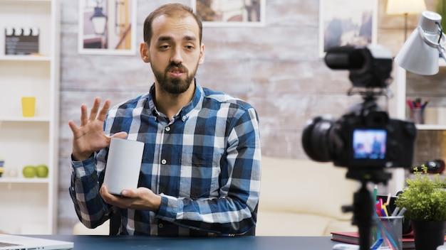 Beroemde vlogger filmt smart speaker review voor zijn volgers. influencer neemt nieuwe vlog op.