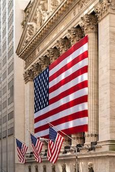 Beroemde wall street en het gebouw in new york, new york stock exchange met patriotvlag