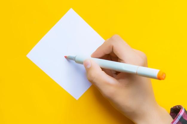 Beroemdheidshand die de handtekeninghandtekening geven die op geel, minimalistisch creatief concept g wordt geïsoleerd
