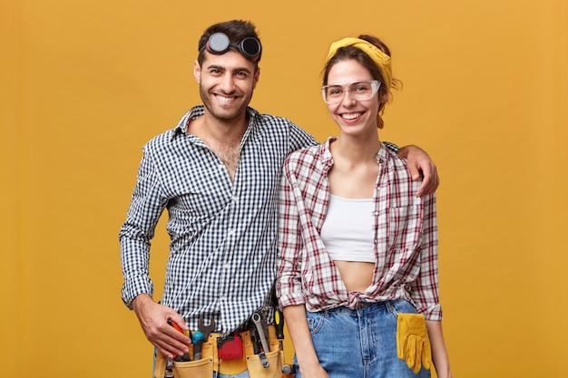 Beroep, beroep, teamwerk en baanconcept. positieve onderhoudsmedewerkers die graag samenwerken en mensen helpen bij het repareren en repareren van dingen