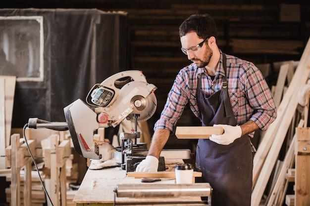 Beroep, timmerwerk, het concept van houtbewerkingsmensen - timmerman met houten plank en notitieboekje die zijn nota's controleren op workshop