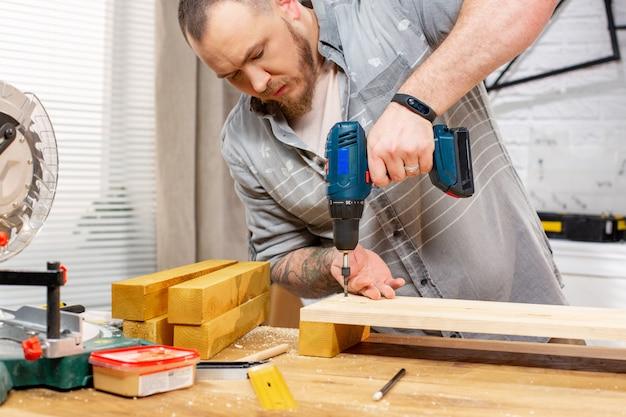 Beroep, timmerwerk, houtbewerking en mensenconcept - timmerman met elektrische boor die houten plank boren op workshop