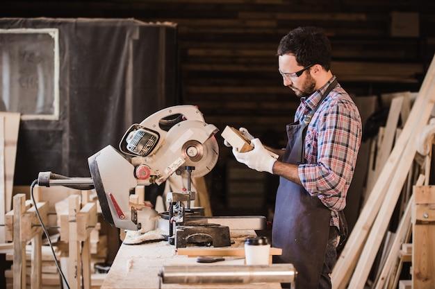 Beroep, timmerwerk, houtwerk mensen concept. timmerman met houten plank en notebook zijn aantekeningen controleren op workshop