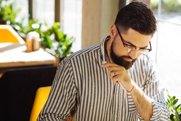 Beroepsberoep. ernstige knappe man die naar de tafel kijkt terwijl hij zich op zijn werk concentreert