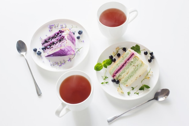 Berry cheesecakes en twee kopjes thee op witte tafel