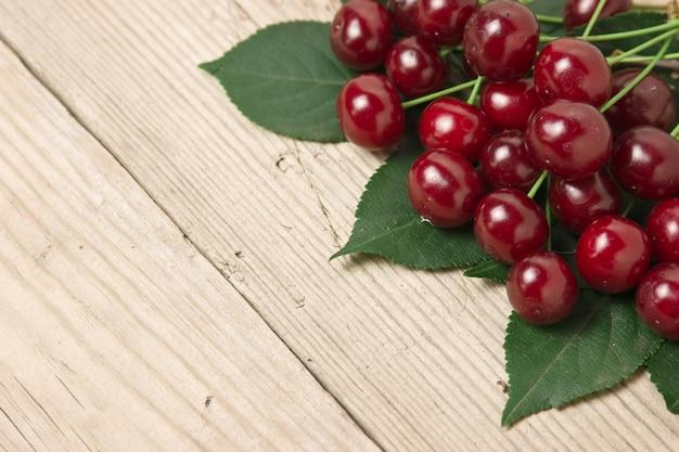 Berry cherry met bladeren op een houten achtergrond