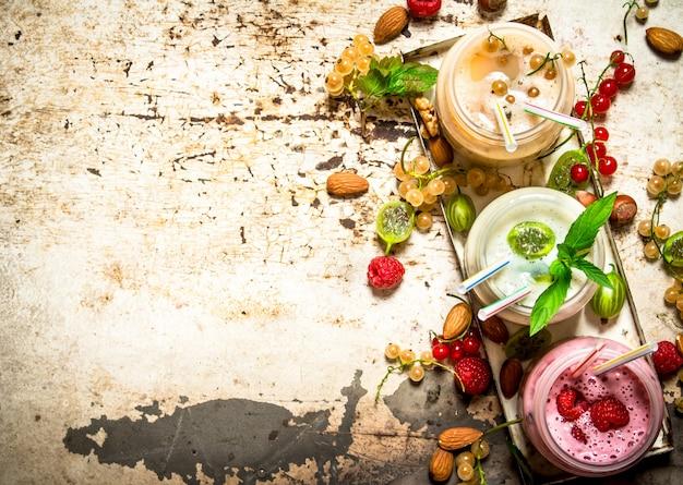 Berry smoothie gemaakt van aalbessen, kruisbessen en frambozen met noten op rustieke tafel.