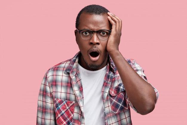 Beschaamd aantrekkelijke afro-amerikaanse man met geschokte uitdrukking, gekleed in een geruit overhemd en bril, drukt grote verbazing uit, geïsoleerd over roze