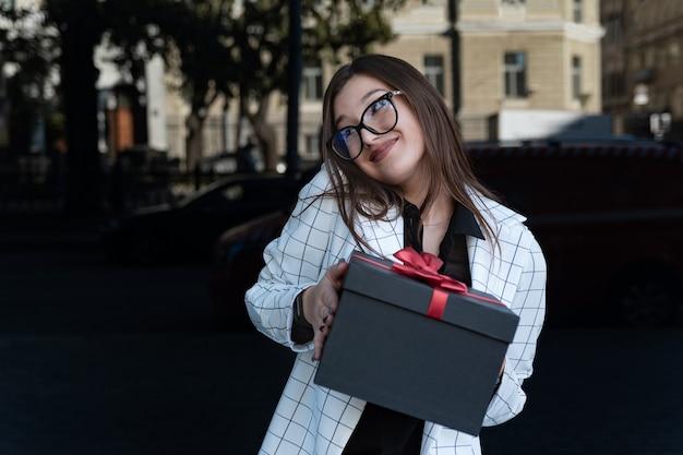Beschaamd gelukkig jong meisje met cadeau in haar handen glimlacht. jonge vrouw houdt netjes zwarte doos met rode strik.