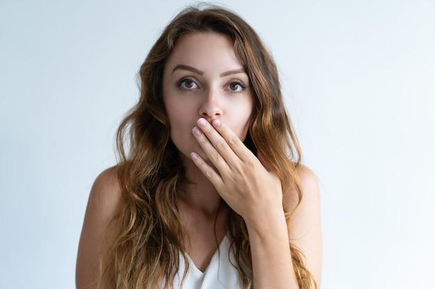Beschaamd mooie jonge vrouw die mond met hand behandelt