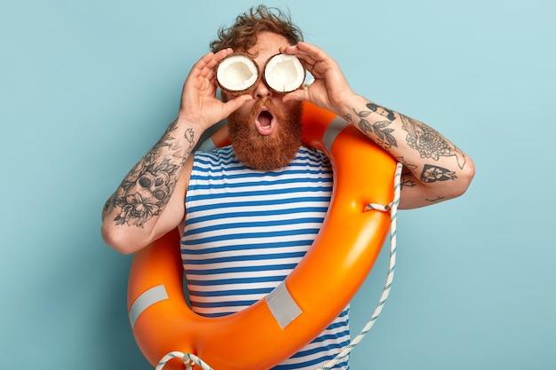 Beschaamd roodharige jongeman met dikke baard, houdt kokosnoot op ogen, kijkt in de verte