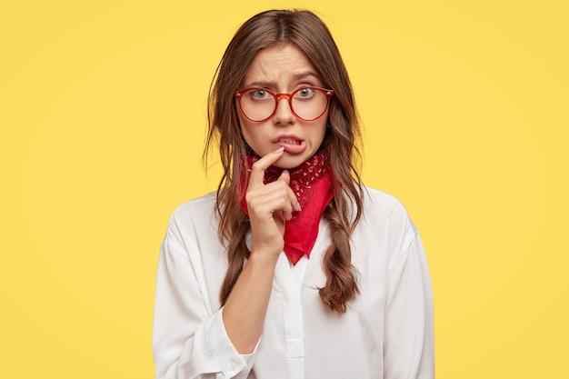Beschaamde hipster of vrouwelijke tiener heeft een ontevreden gezichtsuitdrukking, houdt de wijsvinger bij de lippen, kijkt gefrustreerd