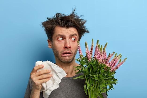 Beschaamde jongeman kijkt verrassend naar plant die allergie veroorzaakt, houdt zakdoek vast voor loopneus, heeft een gevoelig immuunsysteem, rommelig haar, rode zwellende ogen, poseert tegen een blauwe muur